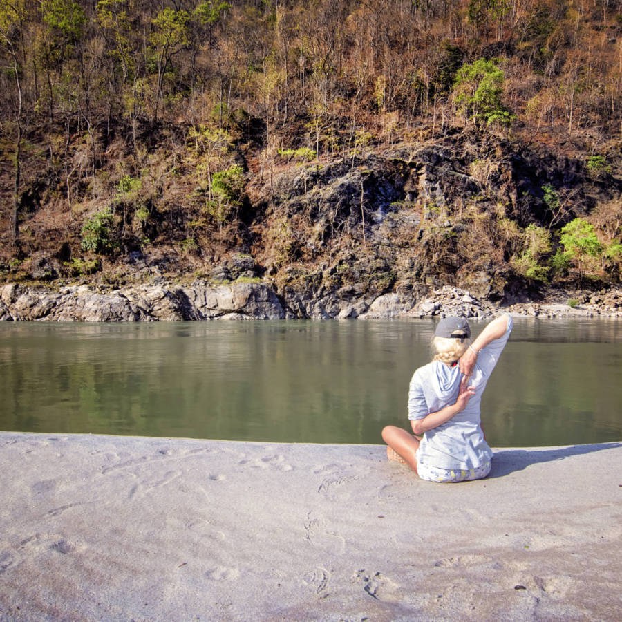 Image of lady stretching on beach on Karnali River in Nepal